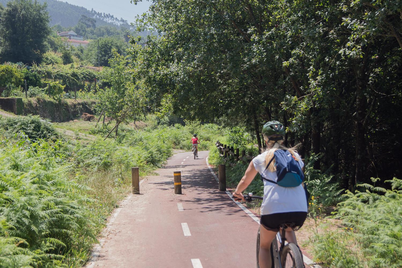 Duas pessoas a andar de bicicleta na ecopista do Vouga