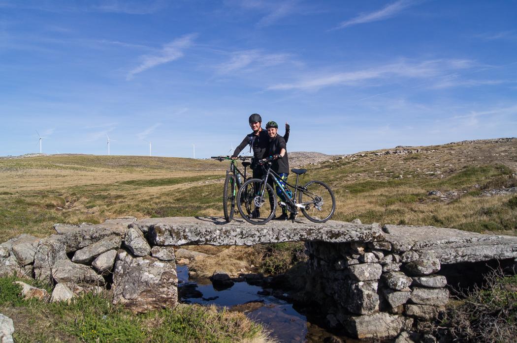 pessoas com bicicleta em cima de uma ponte de pedra na serra