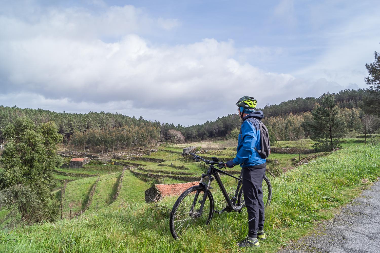 um ciclista a olhar para o paisagem na serra de ladário
